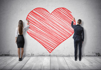 Businessman and businesswoman drawing big red heart on concrete wall