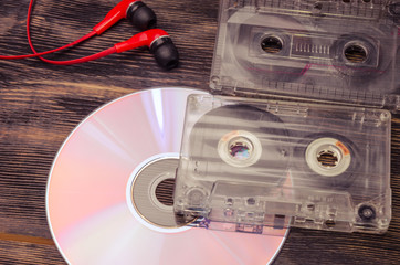 Retro compact cassette with disc and headphones on wood.