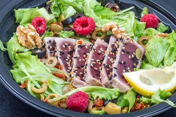 tuna sashimi with fresh salad with raspberry, nut and green olives