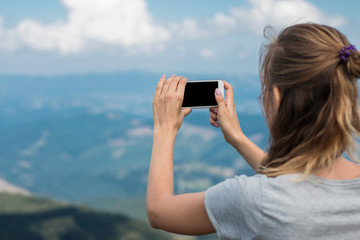 The girl photographed on a smartphone mountains