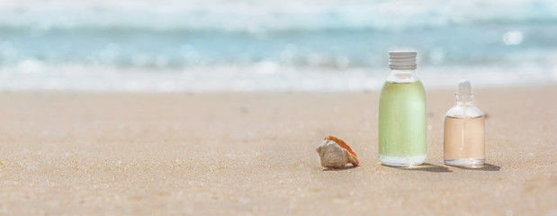 Bottles with oil essence and shell in the sea waves. Spa and wellness setting.