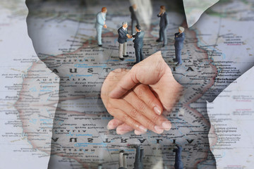 Double exposure of handshake and Selective focus of miniature businessman handshake on Australia map background as Partnership, relationship, handshake and commitment concept.