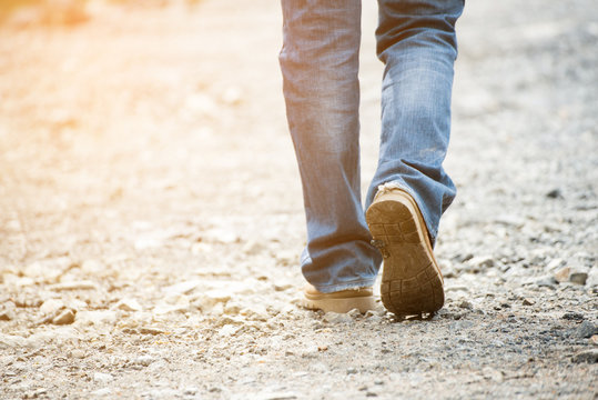 Legs of Lonely man wearing jeans and leather boots walking along the path strewn with rocks. Travel Concept