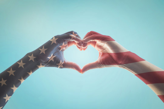 USA patriot, veterans, independence day with American flag pattern on people hands in heart love shape isolated on blue sky