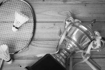 Shuttlecocks, racket and badminton trophy on wood background with monochrome image