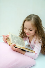 Little girl with story book in bed
