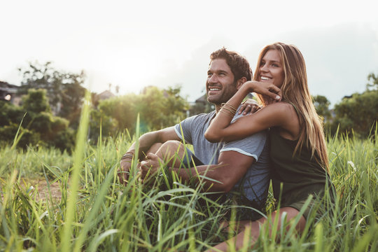 Affectionate young couple sitting on rural grass