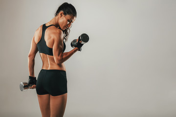 Fit strong young woman lifting weights
