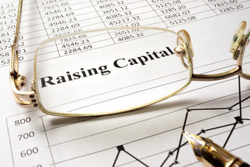 Sign raising capital on a paper and glasses. Wall mural