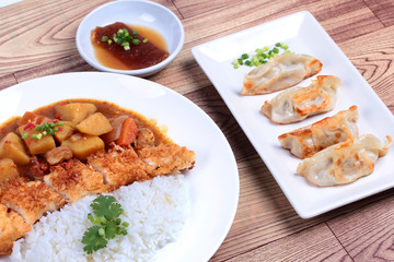 Rice with deep fried dolly fish in japanese yellow curry and side dish of gyoza.