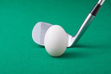 卵のボールとゴルフクラブ(アイアン)