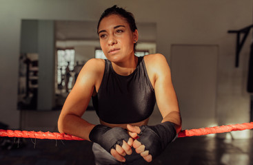 Thoughtful female boxer leaning on ropes