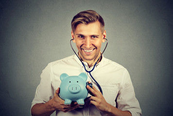 Happy successful man listening to piggy bank with stethoscope