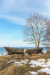 Old wooden boat at coast by winter