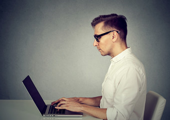Side profile young man using a laptop computer