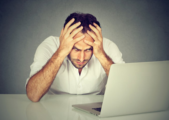 Stressed young man sitting at his desk in front of computer