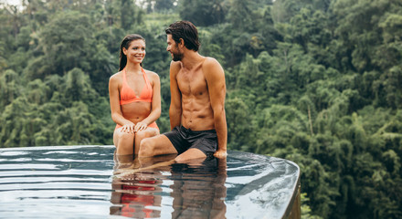 Couple relaxing in resort swimming pool