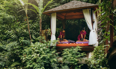 Couple having massage at spa resort surrounded by trees