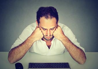 Sad young man sitting at table looking at computer keyboard