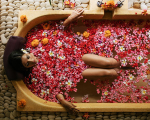 Woman taking flower bath at spa center
