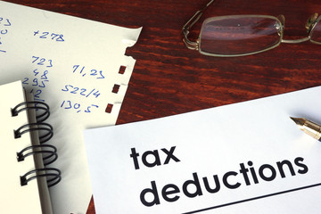 Tax deductions written on a paper. Financial concept.