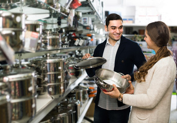 couple chooses pans in shop cookware