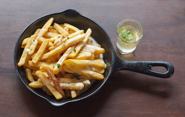 French fries in the pan on table with sweet sauce