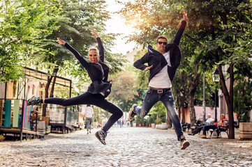 Attractive woman and handsome man with sunglasses having fun and jumping on the street. Fashion lifestyle