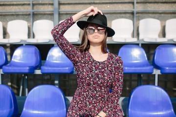 Girl in dress posing in the stadium