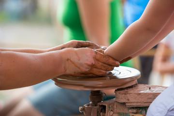 Female hand helping to make ceramic jug on a wheel children's ha