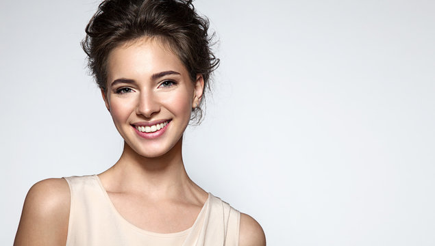 Beautiful smiling woman with clean skin, natural make-up, and white teeth on grey background