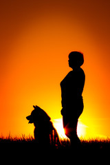 Silhouette of woman with dog on the beach, sunset background