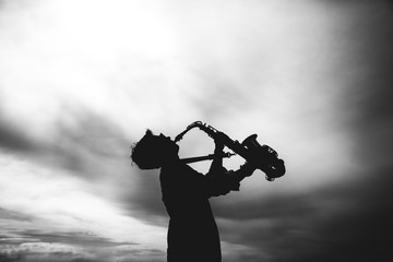 Silhouette of young woman playing the saxophone