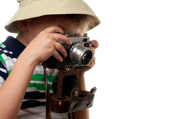 Little boy shooting on the vintage photo camera