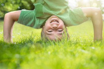 Young boy doing a headstand on the grass