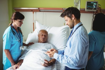 Male doctor showing report to senior patient on digital tablet