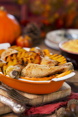 Oven roasted chicken with grilled pumpkin on a rustic table