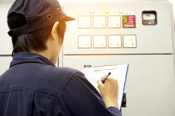 Technician is recording data Voltage or current in control panel
