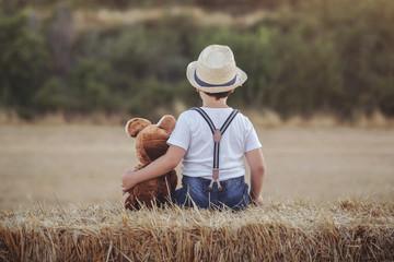 niño abrazado a su oso de peluche