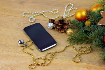 phone greetings.Smartphone and Christmas tree on wooden backgrou