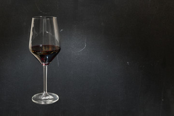Glass of red wine on dark chalkboard