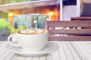Cups of hot smile coffee on white wood table with wood chair in natural resort, vintage tone background.