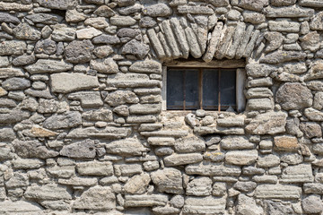 Small window with bars in stone wall