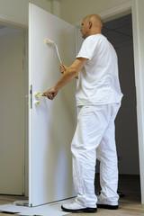 Handwerker beim lackieren einer Tür in einem Bürogebäude