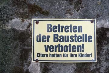 """Schild an einer Baustelle mit den Worten """"betreten der Baustelle verboten"""""""