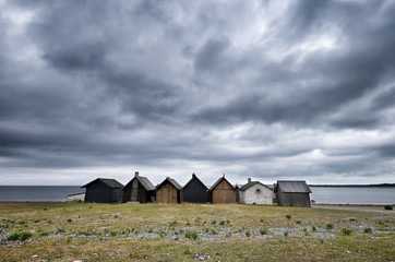 Row of old fishing shacks on the Baltic Sea under stormy sky