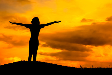 Happy young woman silhouette with twilight sunset.