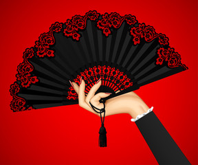 Female hand with open black vintage fan isolated on red light