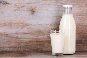 Milch im Glas und in der Flasche auf Holz Stein Hintergrund.