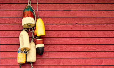 Vintage lobster floats on old red wood siding background. Nautical